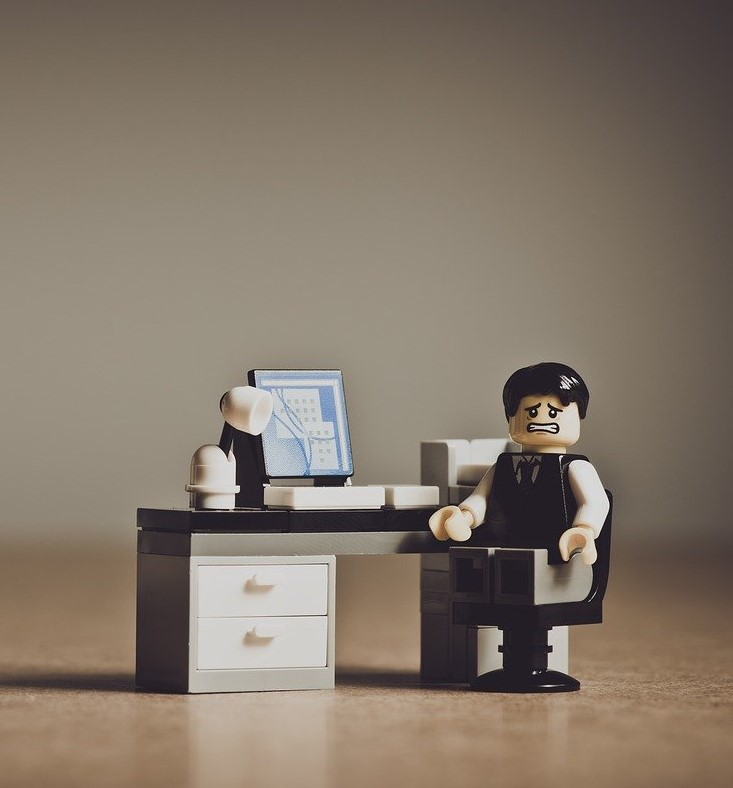 lego man at desk looking scared